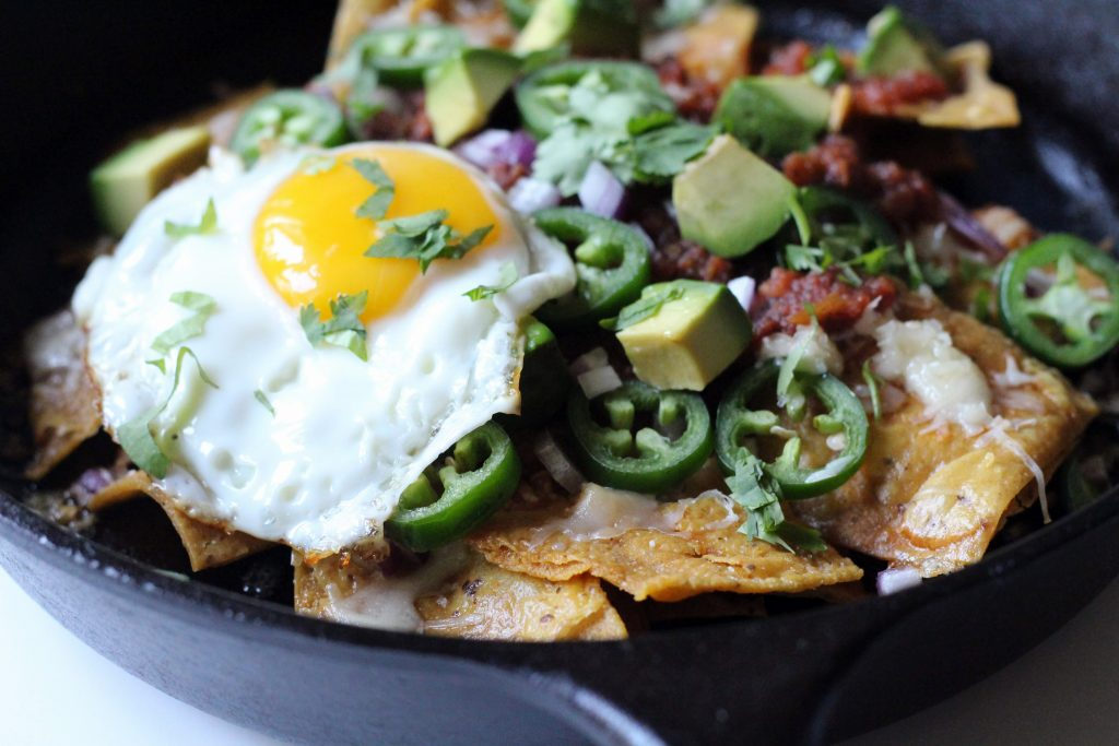 Close up of tortilla chips in a cast iron pan, with jalapenos, salsa, avocado, cilantro, and a fried egg on top.