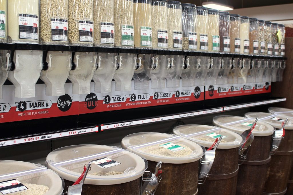 row of wooden barrels and bulk dispensers filled with bulk grocery items.