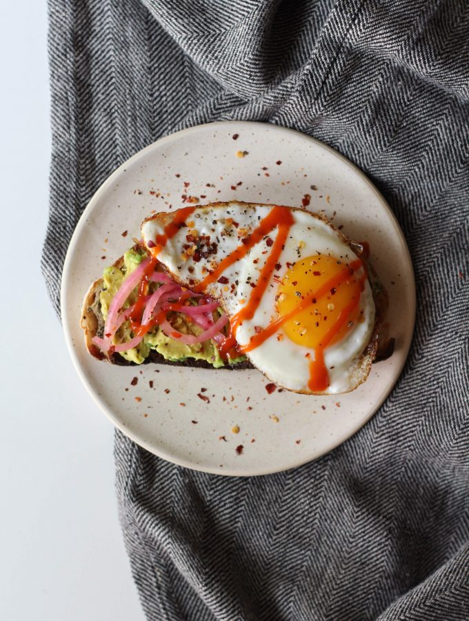 sourdough toast with avocado, pickled onions, and egg on top. topped with crushed red peper.